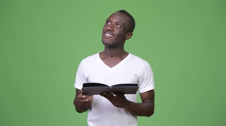 diary : Young African man reading book and thinking Stock Footage