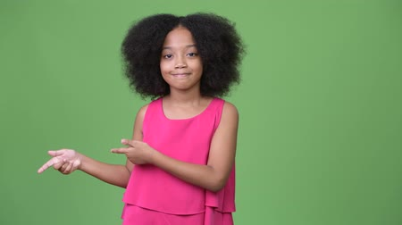kıvırcık saçlar : Young cute African girl with Afro hair showing something