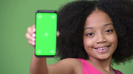 pink background : Young cute African girl with Afro hair showing phone