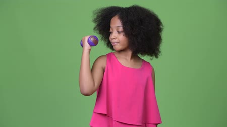 kıvırcık saçlar : Young cute African girl with Afro hair exercising with dumbbells