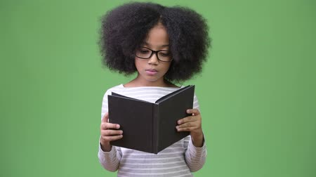 literatura : Young cute African girl with Afro hair studying against green background Stock Footage