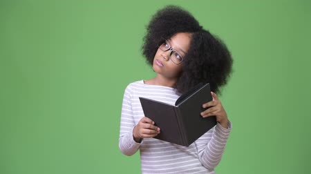 книга : Young cute African girl with Afro hair studying against green background Стоковые видеозаписи