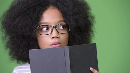 shy : Young cute African girl with Afro hair studying against green background Stock Footage
