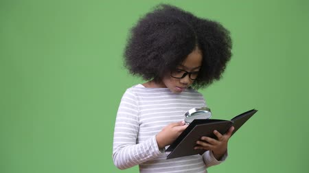 diary : Young cute African girl with Afro hair studying against green background Stock Footage