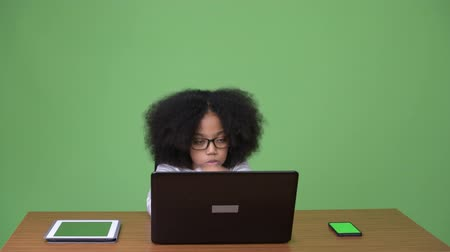 Young cute African girl with Afro hair using laptop Dostupné videozáznamy