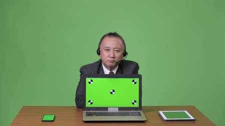 representante : Mature Japanese businessman working as call center representative
