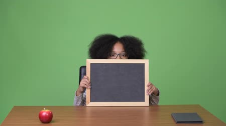 kıvırcık saçlar : Young cute African girl with Afro hair showing blackboard while sitting