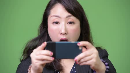 удивленный : Mature beautiful Asian businesswoman using phone and looking shocked