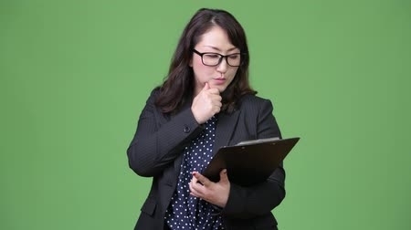 tiro do estúdio : Mature beautiful Asian businesswoman with clipboard