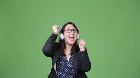 nerd : Mature beautiful Asian businesswoman listening to music