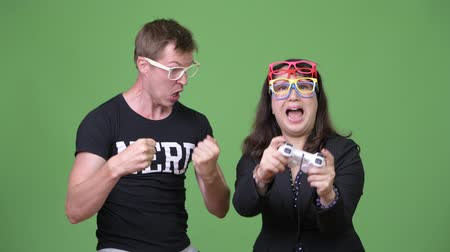 raising fist : Mature Asian businesswoman and young Scandinavian nerd man playing games together