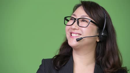 representante : Mature beautiful Asian businesswoman working as call center representative
