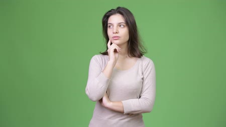 dospělý : Young beautiful woman thinking against green background