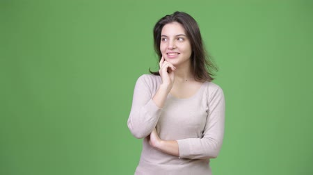 hand on chin : Young happy beautiful woman thinking against green background