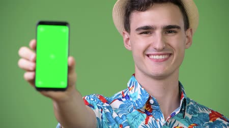 гавайский : Young handsome tourist man showing phone