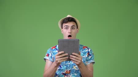 гавайский : Young handsome tourist man using digital tablet and looking shocked