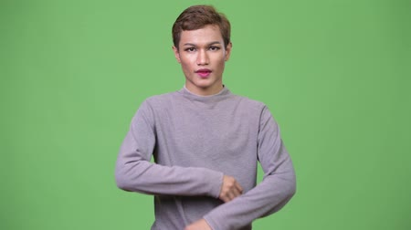 výstřední : Happy young androgynous Asian man with arms crossed