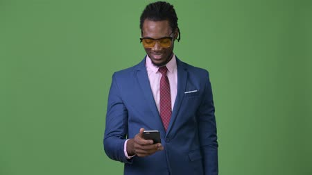 hippi : Young handsome African businessman with dreadlocks against green background Stock mozgókép