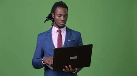 hippi : Young handsome African businessman with dreadlocks against green background Stok Video