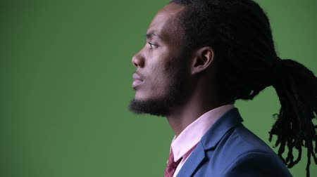 profil : Young handsome African businessman with dreadlocks against green background Wideo