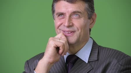 hand on chin : Mature handsome businessman against green background Stock Footage