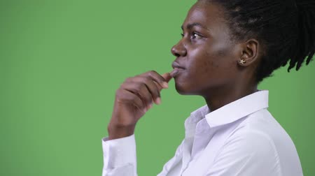 hand on chin : Profile view of young beautiful African businesswoman thinking Stock Footage