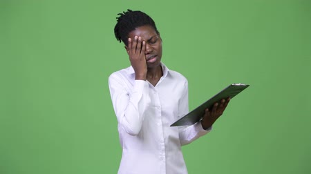 panoya : Young beautiful African businesswoman reading on clipboard Stok Video