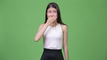 délkelet Ázsia : Young beautiful Asian businesswoman covering mouth while looking guilty