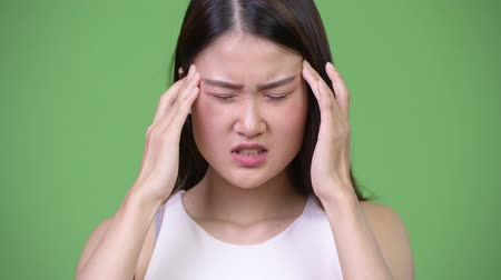 migrén : Young beautiful Asian businesswoman having headache Stock mozgókép