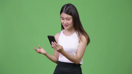 délkelet Ázsia : Young beautiful Asian businesswoman using phone Stock mozgókép