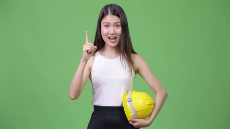 délkelet Ázsia : Young beautiful Asian businesswoman as engineer pointing up