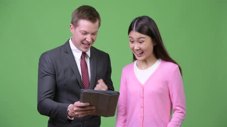 raising fist : Young Asian woman and young businessman using digital tablet together
