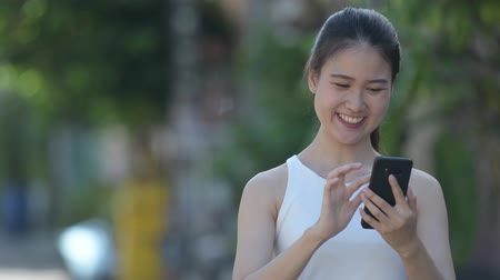 chodník : Young happy beautiful Asian businesswoman using phone outdoors