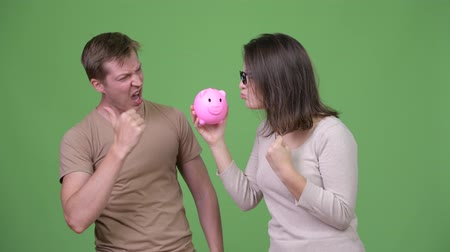raising fist : Young couple holding piggy bank and giving thumbs up together