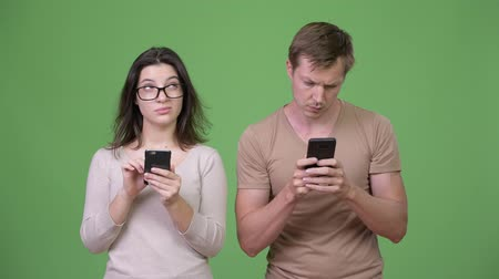 hand on chin : Young couple using phone and thinking together Stock Footage