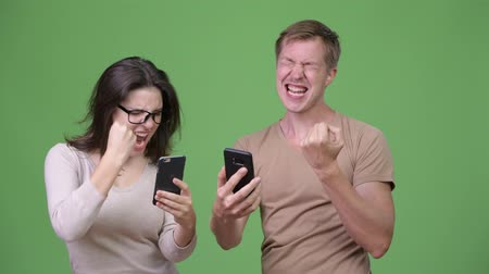 torcendo : Young couple using phone and getting good news together