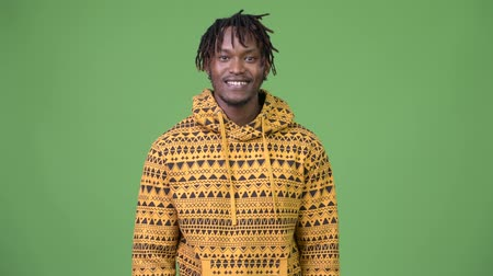hippi : Young happy African man against green background Stok Video