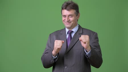 duruş : Mature handsome businessman against green background Stok Video