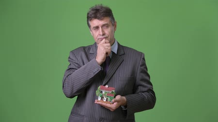 ипотека : Mature handsome businessman against green background Стоковые видеозаписи