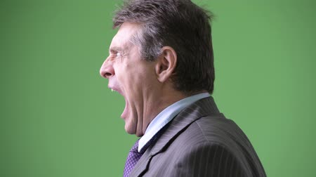 perfil : Mature handsome businessman against green background Stock Footage