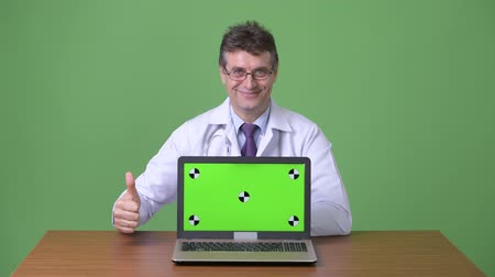 polegar : Mature handsome man doctor against green background