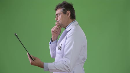 hand on chin : Mature handsome man doctor against green background