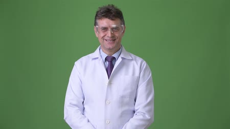 lab coat : Mature handsome man doctor against green background