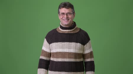 sweater : Mature handsome man wearing turtleneck sweater against green background Stock Footage
