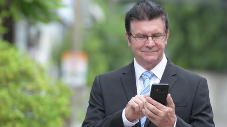 chodník : Happy handsome senior businessman using phone in the streets outdoors