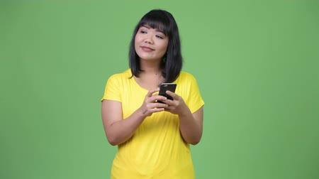 malajské : Beautiful happy Asian woman thinking while using phone