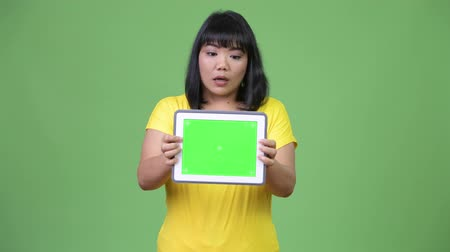 malajské : Beautiful Asian woman showing digital tablet and looking shocked Dostupné videozáznamy