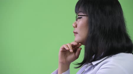 hand on chin : Profile view of beautiful happy Asian woman doctor thinking