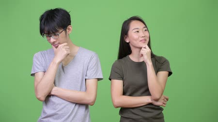 hand on chin : Young Asian couple thinking together