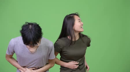 gyomor : Young Asian couple having stomach ache together Stock mozgókép
